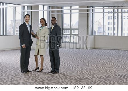 Multi-ethnic business people posing in empty building