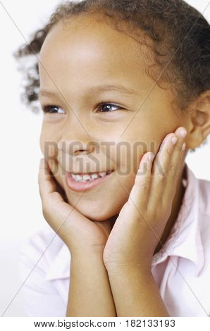 Close up of mixed race girl smiling with head in hands