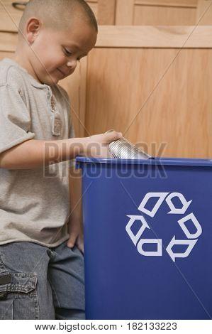 Hispanic boy recycling tin can