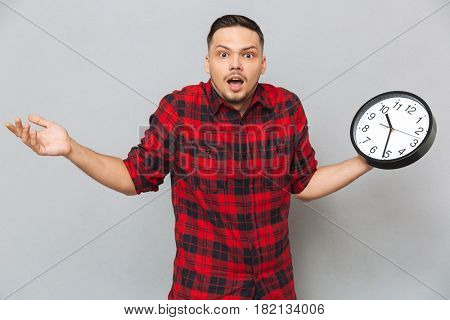 Incomprehensible man in shirt holding clock and looking at the camera over gray background