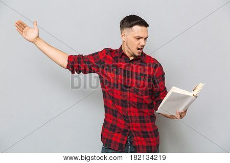 Concentrated man in red shirt rehearses with book in studio over gray background
