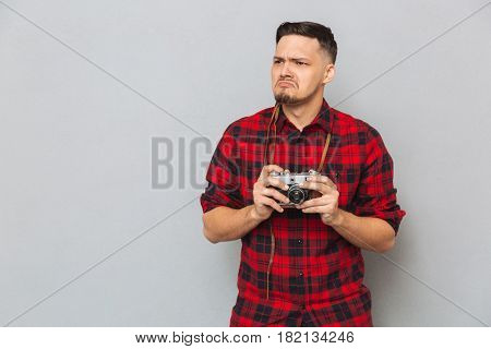 Displeased man in shirt holding retro camera and looking away over gray background