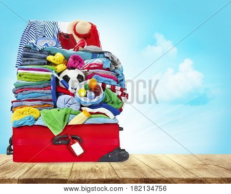 Suitcase Full Of Clothes Open Luggage with Travel Baggage on Wood Table