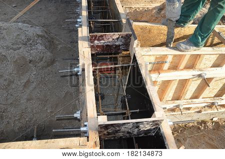 Foundation construction. Foundation building. Concrete foundation with wooden slabs and contractor.
