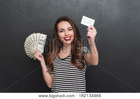 Image of smiling young lady standing over grey wall and holding money and debit card in hands. Looking at camera.