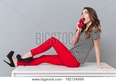 Picture of thinking young lady sitting on table over grey wall talking by phone. Looking aside.