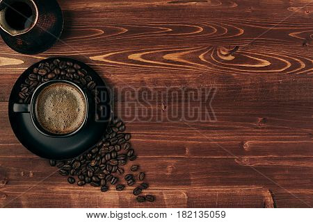 Hot coffee in black cup with crema beans and turkish pot cezve with copy space on brown old wooden board background top view. Rustic style.