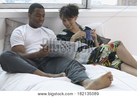 African couple doing crossword puzzle in bed