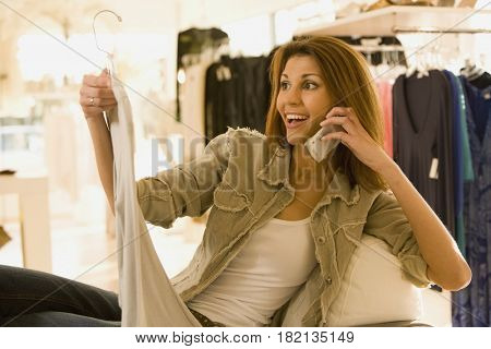 Mixed race woman shopping while talking on cell phone