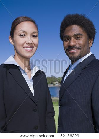 Businessman and businesswoman outdoors smiling