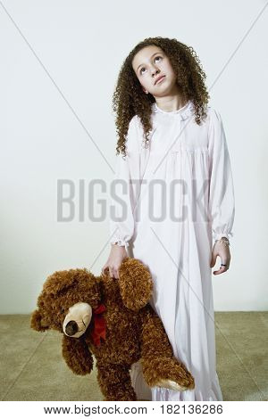 Mixed race girl in nightgown with teddy bear