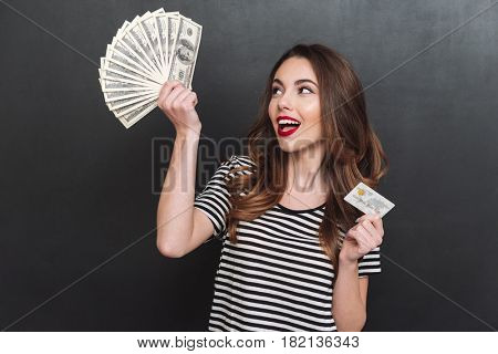Image of happy young lady standing over grey wall and holding money and debit card in hands. Looking aside.