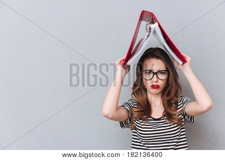 Picture of sad young lady standing over grey wall holding folder over head. Looking at camera.