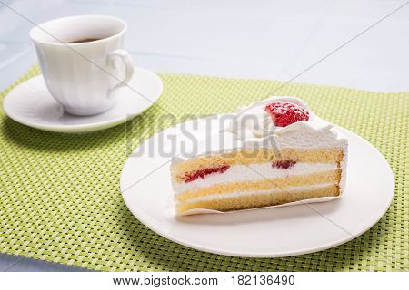 Cut a layer cake with strawberry on white plate in front of cup