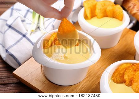 Female hand dipping chip in bowl with beer cheese dip, closeup