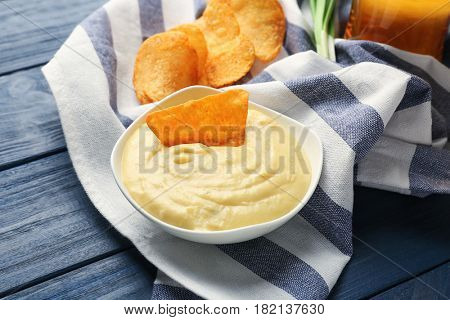Bowl with beer cheese dip and nacho on wooden background
