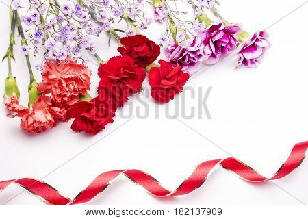 Three types carnations bouquet with two color ribbons on white background