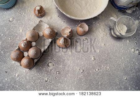 Baking cake ingredients. Bowl flour broken eggs egg shells scattered on the flour.