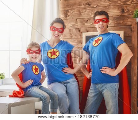 Mother, father and their child are playing together. Girl, daddy and mom in Superhero costumes. Mum, dad and kid are having fun, smiling and hugging. Family holiday and togetherness.