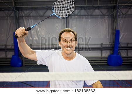 Smiling man in glasses with badminton racket at sports ground.