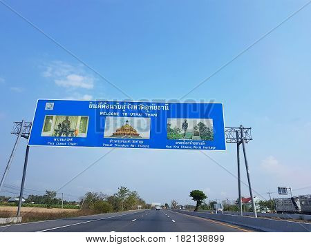UTHAI THANI THAILAND - MARCH 31 : directional traffic sign on highway Welcome to Uthai Thani province with clear blue sky on March 31 2017 in Uthai Thani Thailand.