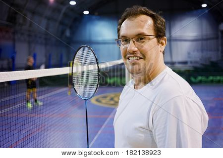 Smiling man in glasses with badminton racket near net at sports ground.