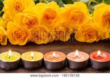 Lined candles with fire in front of yellow rose flowers