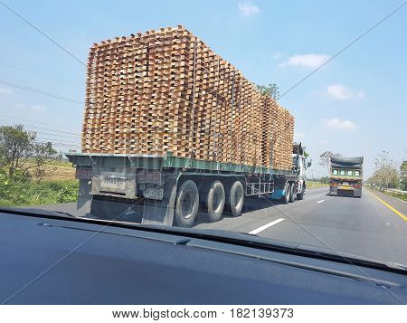 KAMPHAENG PHET THAILAND - MARCH 31 : POV truck carrying lumbers on the highway on March 31 2017 in Kamphaeng Phet Thailand.