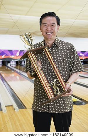 Asian man with bowling trophy