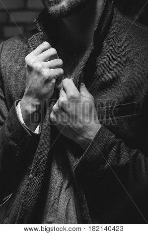 Man holding his jacket collar. Dramatic portrait of a young man pulling his jacket by collar. Man holding both hands on his tuxedo jacket