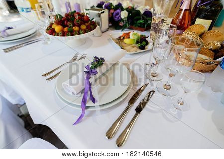 White napkin with purple flowers on a white empty plate on a dining table. Table setting. Table served for wedding banquet close up view