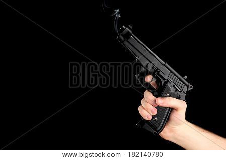 Male hand holding smoking gun on black background