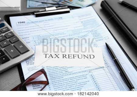 Paper sheet with text TAX REFUND and documents on table