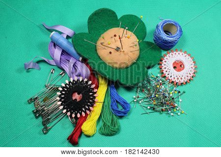 Sewing necessary/ These are sewing necessary on green textile background.