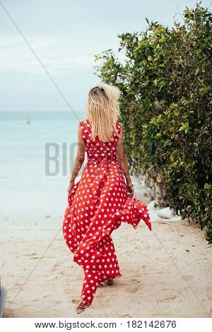 Beautiful young woman with long blond hair in long red dress goes along the beach. Girl in red dress. Long red dress flutters in the wind