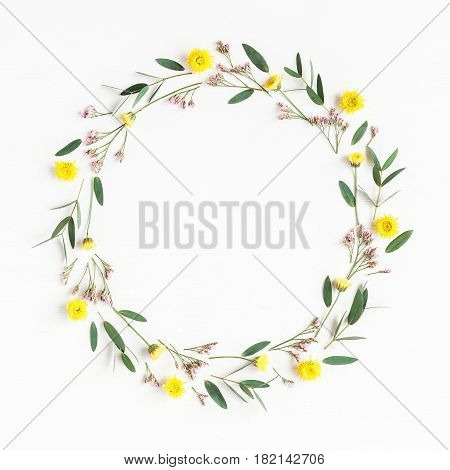 Flowers composition. Wreath made of yellow flowers and eucalyptus leaves on white background. Flat lay top view