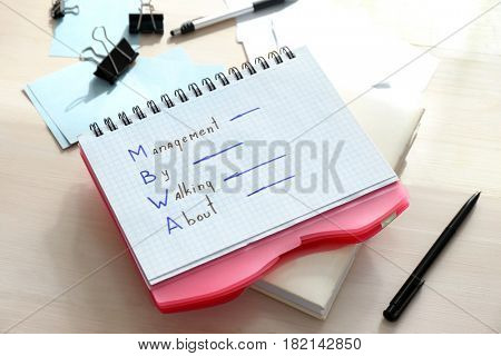 Notebook with written text MANAGEMENT BY WALKING ABOUT on wooden table