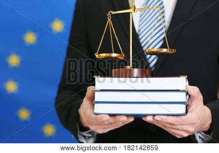 Man holding scales and law books on European Union flag background