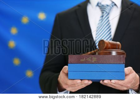 Man holding judge gavel and law books on European Union flag background