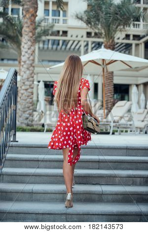 A girl with long straight hair in red dress with polka dots bag and gold high-heeled shoes walking up the stairs