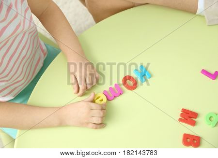 Little girl with teacher constructing word HOME on private lesson