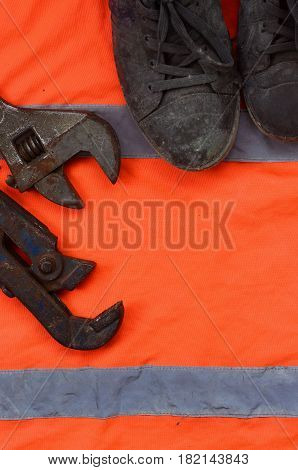 Adjustable Wrenches And Old Boots Lies On An Orange Signal Worker Shirt