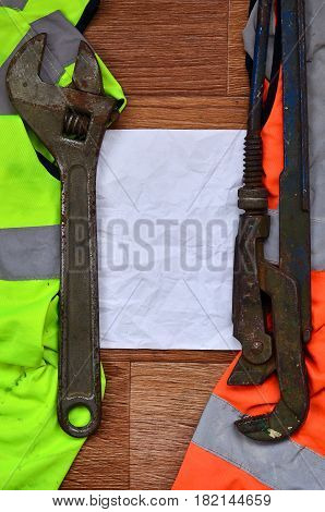Adjustable Wrenches And Paper Lies Of An Orange And Green Signal Worker Shirts