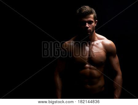 Horizontal portrait of a handsome young muscular fit and toned man posing confidently on black background copyspace workout crossfit fitness athleticism physique endurance confidence motivation.