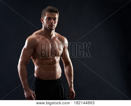Young strong athletic handsome man posing on black background copyspace shirtless male sportsman showing off his ripped fit and toned sexy body cropped studio shot fitness sport motivation concept.