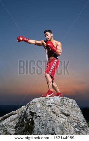 Young aggressive man working out outdoors on sunset boxing punching preparing for fighting fighter martial arts strength power training professional confidence fierce tough masculine muscular
