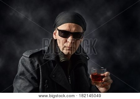 Portrait of a middle-aged man in a black leather jacket sunglasses and black bandana .Rocker with glass of whiskey on black background.
