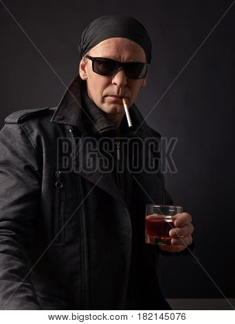 Rocker With Glass Of Whiskey And Cigarette On Black Background.