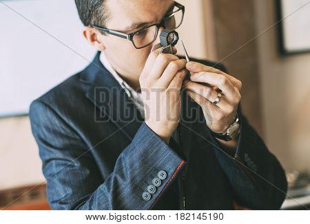 Jeweler examining diamond thoroughly through loupe in shop