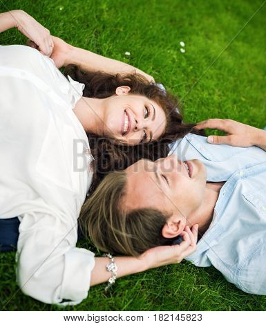 Couple in love lying down on the grass